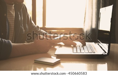 Hand touch screen smart phone and using laptop.Vintage filtered style  - stock photo