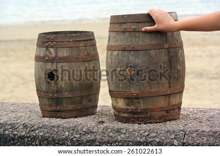 Hand touches an old wooden barrel for distilled beverage at a flea market in Brittany, France - stock photo