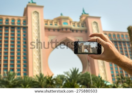 Hand tourist takes a picture of the hotel Atlantis on a mobile phone. Dubai. UAE. - stock photo