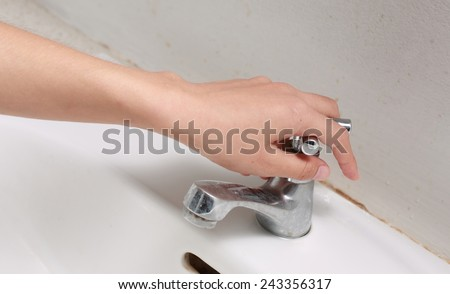 hand Turn off water valves.  - stock photo