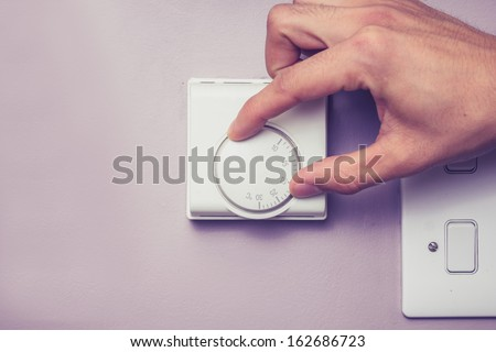 Hand turning dial on thermostat - stock photo