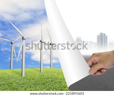 Hand turning gray cityscape page revealing group of wind turbines, alternative energy concept - stock photo
