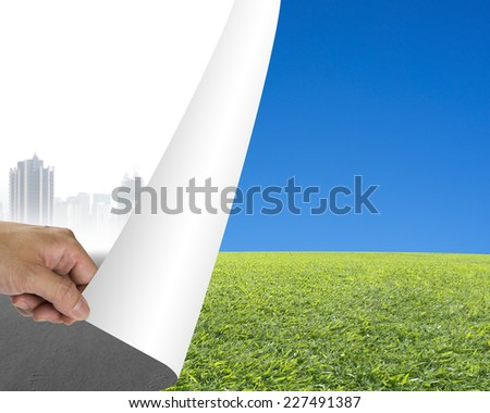Hand turning gray cityscape page revealing nature sky meadow, environmental protection concept - stock photo