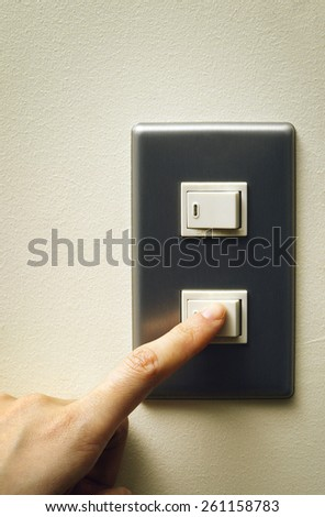 hand turning on the light with a wall switch  - stock photo
