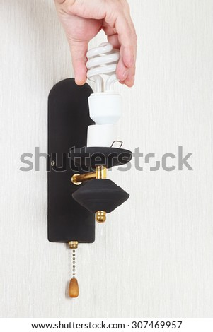 Hand twists tungsten bulb in luminaire on a white wall - stock photo