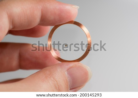 Hand, two Fingers holding round RFID coil Antenna modul - stock photo