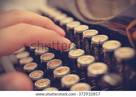 Hand typing on old typewriter, with a retro effect - stock photo