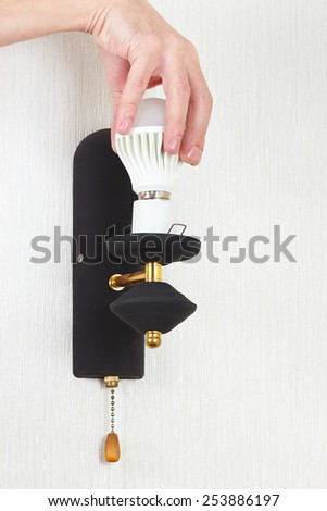 Hand unscrews led bulb in a lamp on a white wall - stock photo
