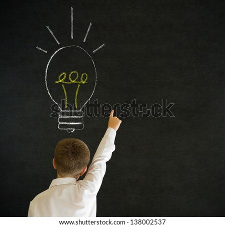 Hand up answer boy dressed up as business man with bright idea chalk background lightbulb on blackboard background - stock photo