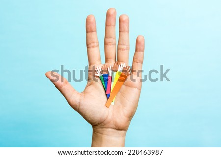 Hand up showing group of diverse multicolors paper hands on blue background. Multiracial concept. - stock photo