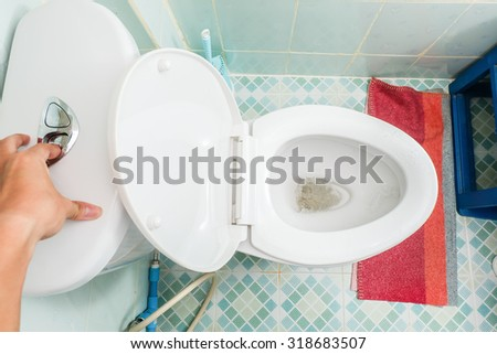 Hand use flush cleaning toilet / Top view - stock photo
