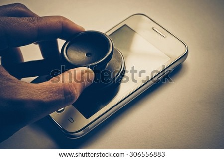 hand using a stethoscope to check smartphone system - checking security on smartphone concept - stock photo