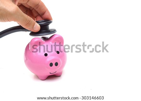 hand using a stethoscope with pink piggy bank - stock photo
