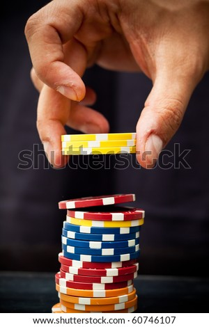 Hand using poker chips - stock photo