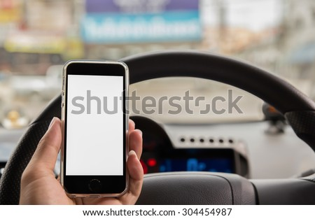 hand using smart phone at steering wheel car - stock photo