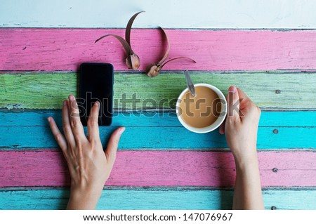hand using smart phone on coffee table - stock photo