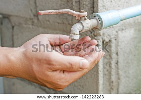 Hand wait for water from old faucet - stock photo