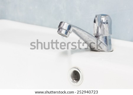 Hand washing basin with grey background  in the bathroom. Flowing water. - stock photo