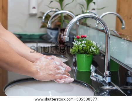 Hand washing with Chrome faucet over the washbasin in modern bathroom - stock photo