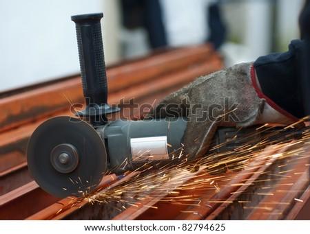 Hand wearing a glove cutting metal - stock photo