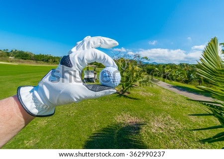 Hand wearing golf glove holding golf ball over beautiful course with the cart, buggy. - stock photo