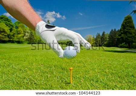 Hand wearing golf glove placing golf ball on the tee over beautiful golf course with blue sky - stock photo