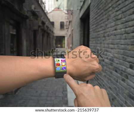 hand wearing ultra slim bent interface smartwatch with apps and day street background - stock photo