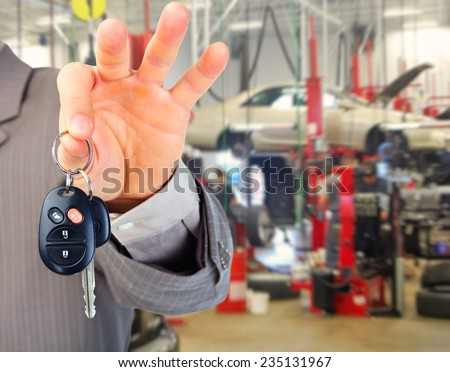 Hand with a car key. Auto repair service - stock photo