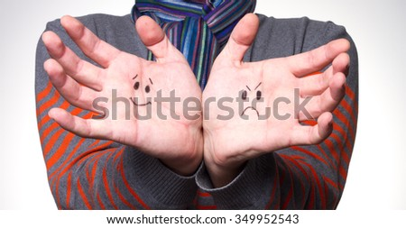 hand with a cheerful and sad smiley - stock photo