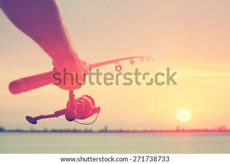 Hand with a fishing tackle against the beautiful sky - stock photo