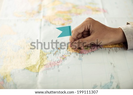 Hand with a flag pin on the map showing destination point - stock photo