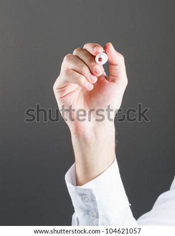 Hand with a marker over blackboard; grey background. - stock photo