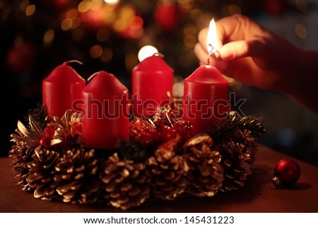 Hand with a match and first advent candle. Selective focus, shallow DOF - stock photo