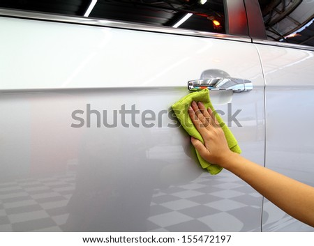 Hand with a microfiber wipe the car polishing - stock photo