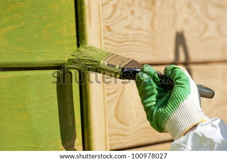 hand with a paint brush painting wooden wall in green outdoor shot - stock photo