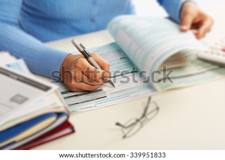 Hand with a pen writing. Accounting and finance background. - stock photo