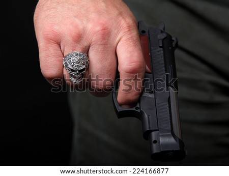 Hand with a ring in the form of a skull holding a handgun, close up - stock photo