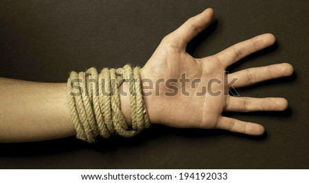 Hand with a rope with black background. Horizontal - stock photo