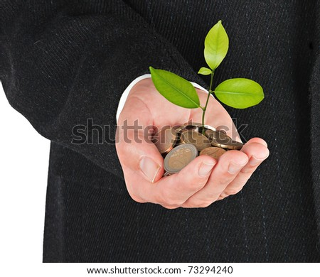 Hand with a sapling growing from pile of coins - stock photo