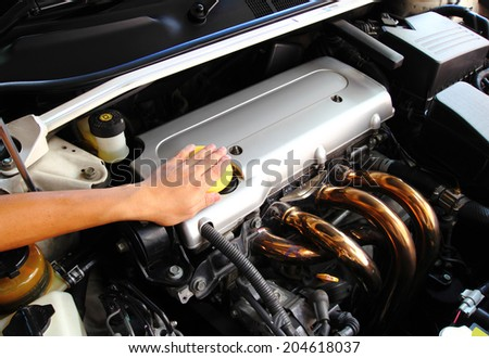 Hand with a sponge wipe the car engine. - stock photo