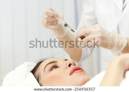 Hand with a syringe over the face, close up. Focus on syringe - stock photo