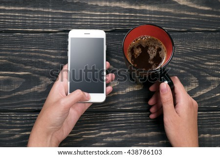 Hand with a white telephone with black and red cup of coffee on the aged wooden dark background - stock photo