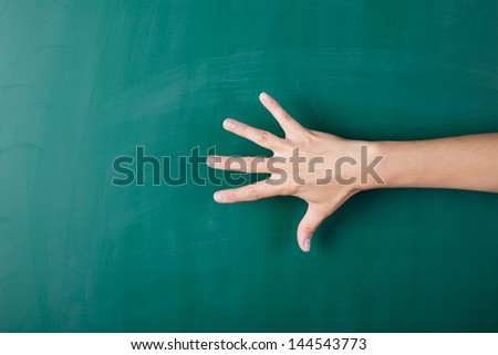 Hand with all five fingers spread on blackboard - stock photo