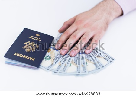 Hand with american passport and dollars on white surface - stock photo