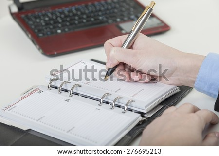 hand with ball pen writes down an appointment into the diary - stock photo