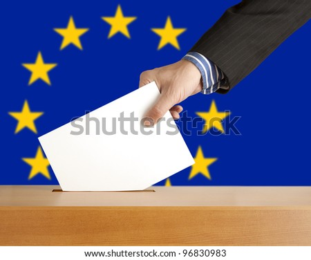 Hand with ballot and box on Flag of Europe - stock photo
