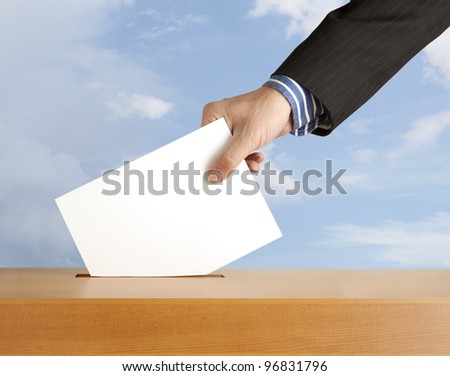 Hand with ballot and box on sky - stock photo