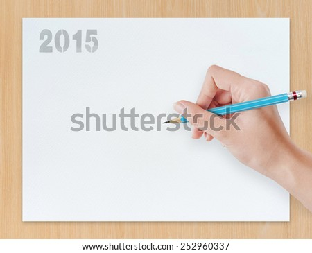 Hand with blue pencil draw something on white paper background. - stock photo