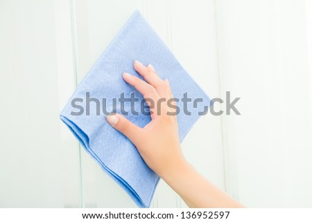 Hand with blue sponge cleaning the bathroom glass - stock photo