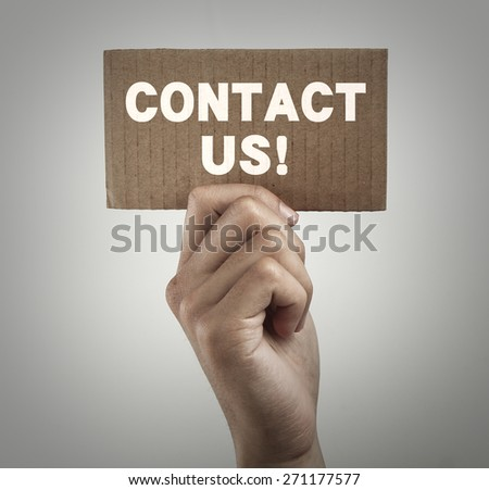 Hand with brown card is showing contact us with gray gradually varied background. - stock photo